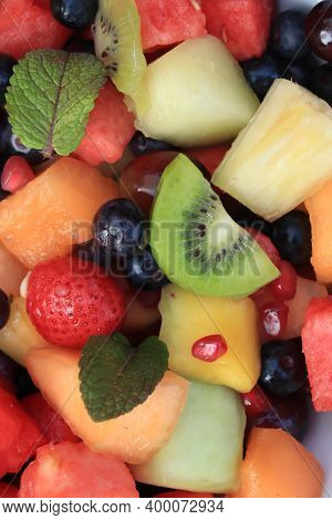 Fresh Juicy Fruit Salad In Bright Colors, Decorated With Fresh Mint Leaves