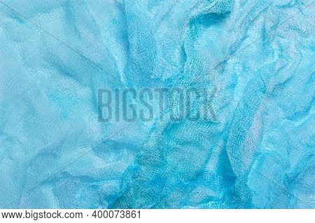 Bright Background Of Crumpled Light Blue Gauze. Used In Design For Decoration