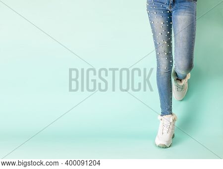 Legs In Tight Jeans And White Winter Sneakers Against The Blue Wall.