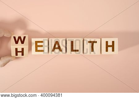 Hand Is Turning A Dice And Changes The Word Health To Wealth. Wooden Blocks With The Word Health And