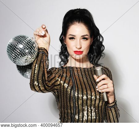 Young woman in evening dress holding microphone and disco ball. Brighrt make up and Wavy hairstyle.