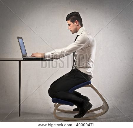 Office worker, at a desk, using a laptop computer