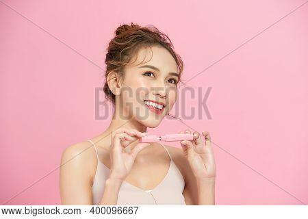 Beautiful Young Woman Close Eyes And Doing Makeup Using A Lip Gloss. Cute Girl Applying Lip Gloss.