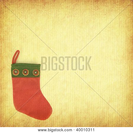 red Christmas stocking on old paper background