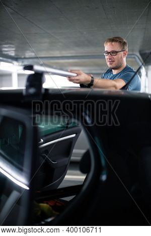 Handsome young driver getting ready to go biking - putting a bike rack on the roof of his car
