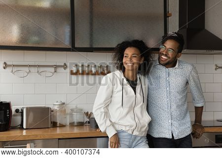 Happy Biracial Couple Dreaming In New Home Kitchen