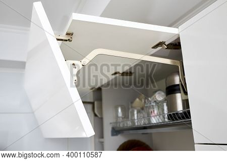 Part Of Contemporary Kitchen Interior. Opened White Horizontal Kitchen Cabinet With Plates And Glass