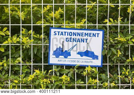 Blue An White Warning Sign On A Fence Stating In French
