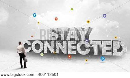 Young businessman standing in front of STAY CONNECTED inscription, social media concept