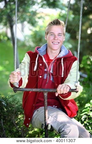 Smiling Teenage Boy sitting on a swing