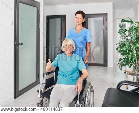 Friendly Geriatric Nurse Assisting Senior Woman In A Wheelchair At Nursing Home Corridor. Medical Ca