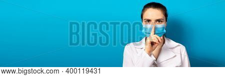 The Doctor In The Mask Shows A Sign Of Silence Finger At The Mouth. Medical Mystery In Medicine And