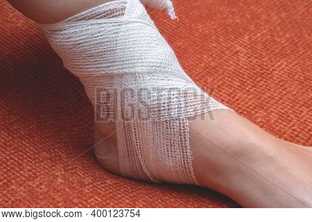 A Young Woman At Home Bandages Her Foot And Lower Leg With A Bandage. Side View, Close-up