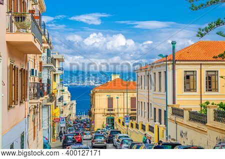 Italy, Reggio Di Calabria, May 11, 2018: Cityscape With Cars In Road And Buildings, Strait Of Messin