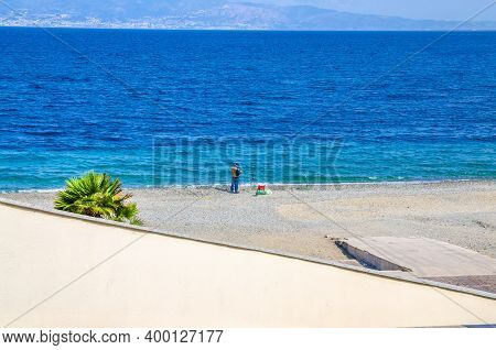 Italy, Reggio Di Calabria, May 11, 2018: Man Is Fishing In Water Of Strait Of Messina Connected Medi