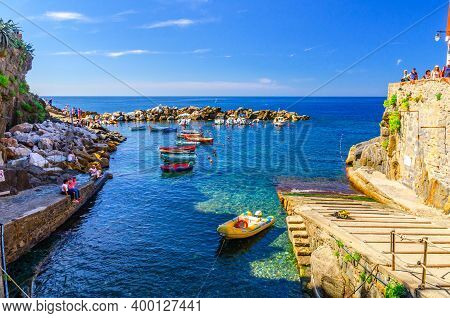 Riomaggiore, Italy, September 12, 2018: Colorful Fishing Boats On Transparent Water In Small Harbor