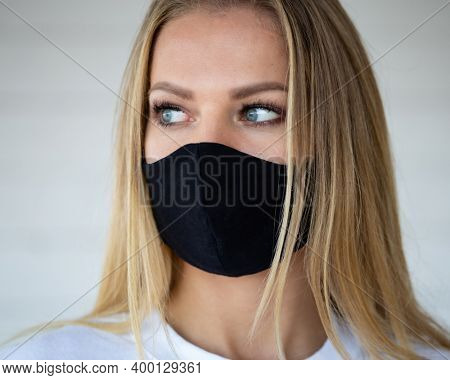A young woman wears a protective mask on her face. It protects itself from coronavirus infection. Personal protection measures during the Covid-19 pandemic. Fashion mockup.