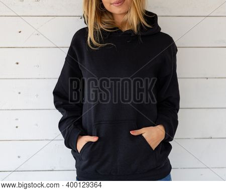 Unrecognizable woman stands in a black sweatshirt against a background of white boards, facing the camera. There is a blank space on the garment for a design, logo or inscription. Fashion mockup.
