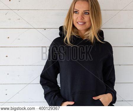 A smiling blonde is standing in a black sweatshirt on a background of white boards, in front of camera. There is a blank space on the garment for a design, logo or inscription. Mockup for clothes.