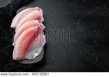 Tilapia Fish Skinless Meat, On Black Background With Copy Space For Text