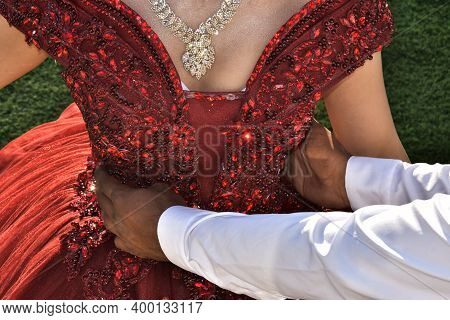 A Scarlet Dress Is On The Bride, The Hands Of The Grooms Man Are Holding The Girl By The Waist. No F