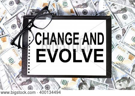 Change And Evolve. Text On White Paper On The Background Of Dollar Bills