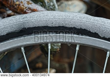 Part Of An Icy Bicycle Wheel With A Black Tire In White Ice And A Gray Spoked Metal Rim