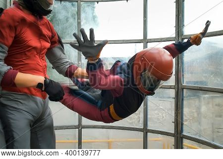 Child Boy With Man Instructor Is Flying In Aerodynamic Tube. Instructor Is Holding Boy By The Specia
