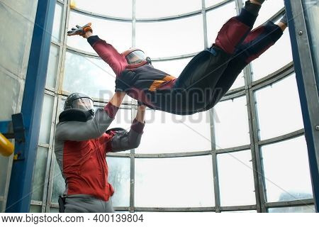 Child Boy With Man Instructor Flying In Aerodynamic Tube, Professional Lesson. Instructor Is Holding