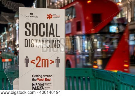 London, Uk - November 3, 2020: A Covid-19 Social Distancing Sign With A Red London Double Decker Bus