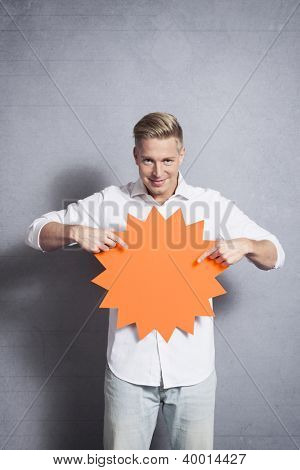 Confident handsome man pointing fingers at blank panel with space for text promoting sales isolated on grey background.