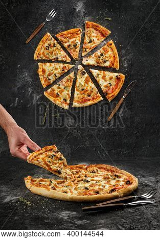 Home Made Original Italian Pizza With Human Hand Holding Pizza Slice. Top View Separated Pizza Slice