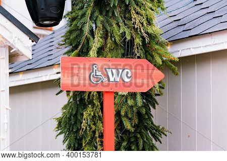 Directional Sign To Wc For Disabled Persons On A Red Wooden Pole With Spruce On The Background. Dire