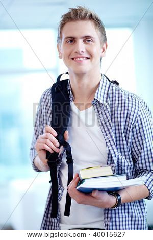 A young guy with backpack and textbooks looking at camera