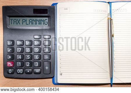 Tax Planning Word On Calculator. Time To Pay Tax In Year. Calculator, Notepad And Pen On A Wooden Ta