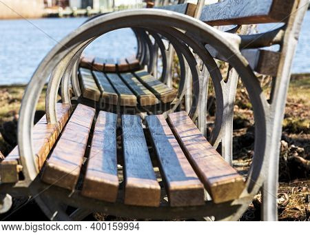View Of Park Benches Looking Through Their Medal Circular Arm Rests.