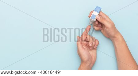 Man Using Lancet For Diabetes, Checking Blood Sugar Level. Wide Image With Copy Space, Blue Backgrou