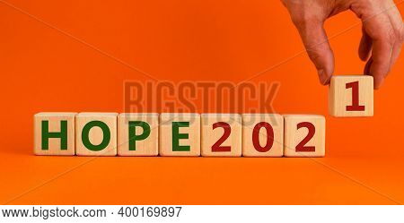 2021 Hope New Year Symbol. Wooden Cubes With Words 'hope 2021'. Male Hand. Beautiful Orange Backgrou