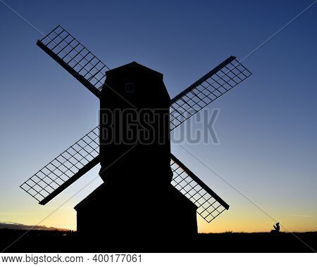 The Girl And The Windmill Silhouette At Sunset Uk.