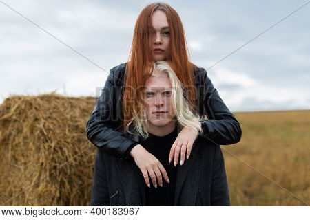 Portrait Of A Couple. An Albino Guy With Blue Eyes In A Black Jacket And A Girl With Bright Red Hair