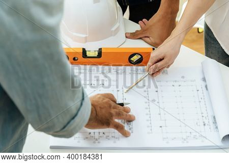 Engineer, Architect, Construction Worker Team Working And Pointing On Drawing Blueprint On Workplace