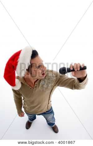 Young Man Wearing Christmas Hat And Singing In To Mic