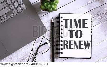 Laptop, And Notepad With Text Time To Renew In Wooden Background