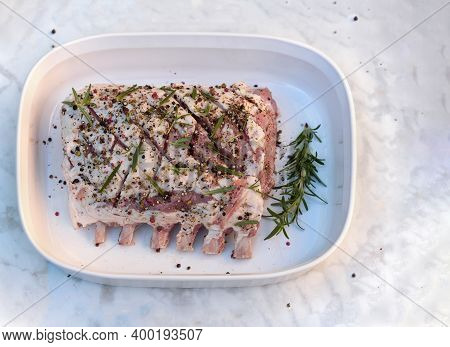 Raw Rack Of Pork With Spices And Rosemary In The Baking Dish. Top View. Flat Lay.
