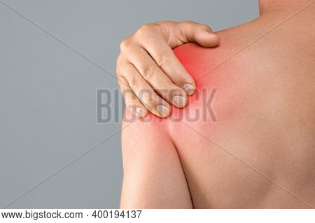 Closeup Of Topless Man Suffering From Shoulder Pain Injury, Rubbing Sore Zone Over Grey Studio Backg