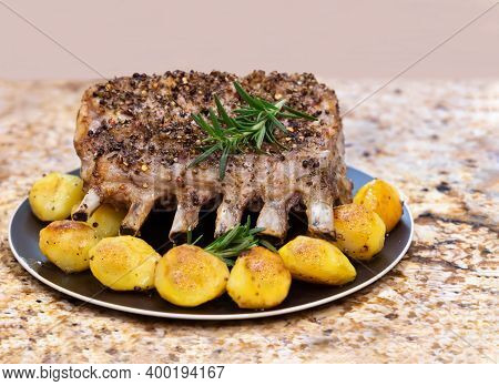 Roast Rack Of Pork With Potatoes And Rosemary On The Black Plate.