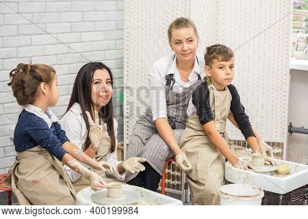 Boy And Girl With Their Mothers At Pottery Wheels In A Pottery Workshop