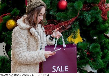 Happy Woman Holds Paperbags With Symbol Of Sale In The Stores With Sales At Christmas, Around The Ci