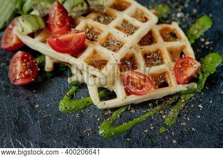 Fresh Baked Belgian Waffles With Arugula, Tomatoes And Avocado On Black A Plate. Savory Waffles. Bre