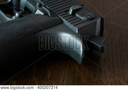 Black Pistol On Wooden Background. Weapons For Sport And Self-defense On Table. Handgun Closeup View